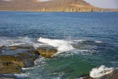 Roccia vigorosa, crolli in un mare blu, con abbagliamento del sole, rocce maestose Immagini Stock