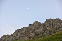 Roccioso contro cielo blu e la bella mezzaluna nella sera Fotografia Stock Libera da Diritti