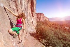 Rocha alaranjada vertical de ascensão do montanhista fêmea do estilo da hippie Fotografia de Stock