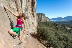 Rocha alaranjada vertical de ascensão do montanhista fêmea do estilo da hippie Imagens de Stock