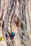 Rocha alaranjada vertical de ascensão do montanhista fêmea louro Imagem de Stock