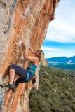 Rocha alaranjada vertical de ascensão do montanhista fêmea louro Foto de Stock