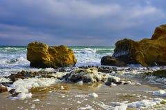 Rocha amarela nas ondas Fotografia de Stock Royalty Free