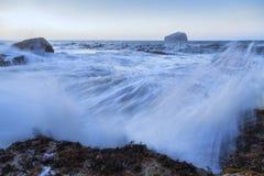 Rocha baixa na distância com um oceano selvagem fotografia de stock royalty free