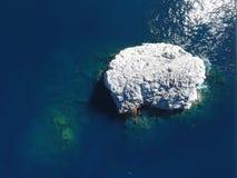 Rocha branca em um oceano azul Imagens de Stock