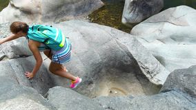 Rocha de escalada do caminhante da jovem mulher na montanha quando caminhada do verão Mulher de viagem com a trouxa que caminha n video estoque