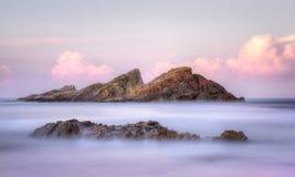 A rocha de Statis fora do selo da baía de Sugarloaf balança NSW Austrália no sunse Foto de Stock