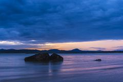Rocha do oceano no nascer do sol na praia imagem de stock