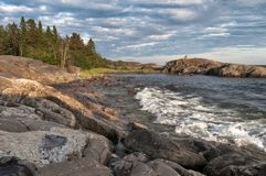 Rocha grande no mar e na floresta azuis do por do sol na distância foto de stock royalty free