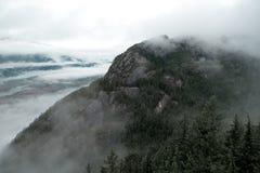 A rocha maciça do granito aparece através da névoa imagens de stock