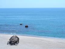 A rocha na praia com o mar imagens de stock