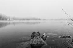 Rocha no lago do outono preto e branco imagens de stock
