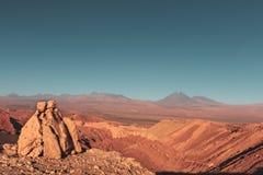 Rocha no meio do deserto de atacama com um vulcão no fundo fotos de stock