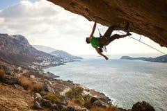 Rocha pendendo sobre de escalada do montanhista masculino fotografia de stock