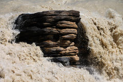Rocha que está contra águas turbulentas Fotos de Stock Royalty Free