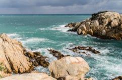 Rochas amarelas que aumentam das profundidades do mar azul esverdeado Foto de Stock Royalty Free