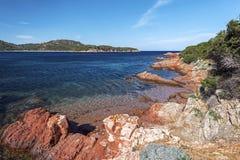 Rochas avermelhadas do litoral da baía de Rondinara Imagem de Stock