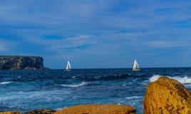 Rochas, barcos de navigação e oceano fotos de stock