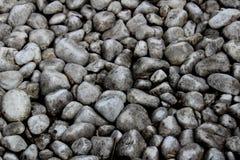 Rochas cinzentas e textura das pedras dos seixos em uma parte externa de superfície natural, com contraste alto com destaques fotografia de stock