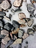 Rochas com terra de derretimento da parte traseira da neve Imagens de Stock Royalty Free
