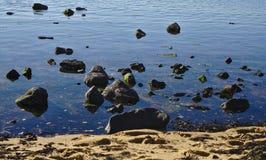 Rochas da praia na água fotografia de stock