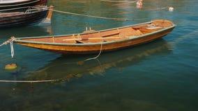 Rochas de madeira pequenas de um barco de pesca em ondas perto da costa filme
