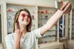 Rochas desta loja do ótico Retrato do blogger fêmea atrativo na loja que tenta em óculos de sol na moda e que mostra a rocha fotografia de stock royalty free
