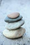 Rochas do equilíbrio na tabela de madeira Fotografia de Stock Royalty Free