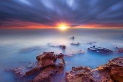 Rochas do por do sol na baía Imagens de Stock
