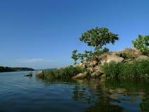 Rochas e árvores na costa de um grande lago Foto de Stock Royalty Free