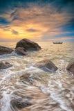 Rochas e barco de pesca de A no por do sol Foto de Stock