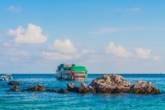 Rochas e barcos de pesca que flutuam no mar azul Foto de Stock