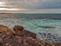 Rochas e ondas em um por do sol Fotografia de Stock