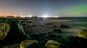 Rochas em um mar liso na noite Luzes do norte Aurora Borealis imagens de stock