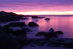 Rochas em um mar nórdico roxo do inverno imagem de stock royalty free