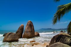 Rochas gêmeas na praia com mar e palmas fotos de stock