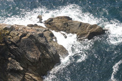 Rochas marrons grandes no mar imagens de stock