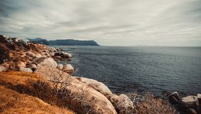 Rochas, montanha e oceano com nuvens imagens de stock royalty free