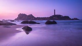 Rochas na praia, nas ondas, na ilha e no farol no nascer do sol imagens de stock royalty free