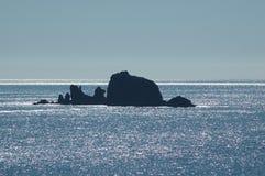 Rochas na silhueta contra um oceano de brilho Foto de Stock Royalty Free