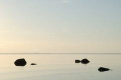 Rochas pretas na água calma Fotografia de Stock Royalty Free