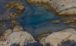 Rochas que cercam a água esmeralda foto de stock royalty free