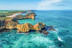 Rochas que estão sendo corroídas pelo martelamento constante de ondas de oceano fotos de stock