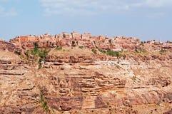 Rochas vermelhas e casas velhas decoradas, as paredes antigas de Kawkaban, Iémen Fotos de Stock
