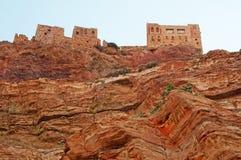 Rochas vermelhas e casas velhas decoradas na estrada a Kawkaban, Iémen Imagens de Stock