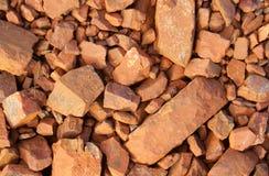 Rochas vermelhas quebradas na terra em uma mina de ferro Imagem de Stock