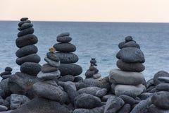 Rochas vulcânicas colocadas no modo da pirâmide, para a apreciação e o abrandamento Este lugar original é ficado situado no porto foto de stock