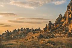 Rochas vulcânicas naturais com as casas antigas da caverna em Cappadocia, Turquia imagens de stock
