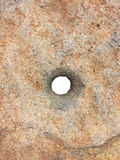 Roche avec un trou au centre images stock