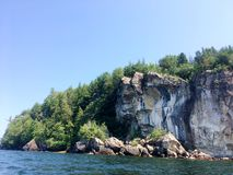 Roche Cliff Face Forested Hill sur un lac Photo stock